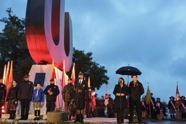 Żołnierze, osoby cywilne i młodzież stoją by uczcić rocznicę upadku Powstania Warszawskiego przed pomnikiem