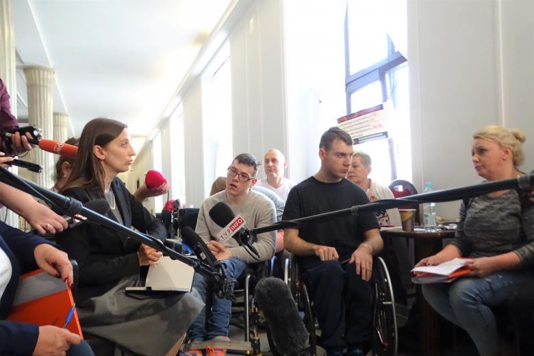 Osoby na korytarzu w Sejmie podczas protestu rodziców dorosłych osób niepełnosprawnych