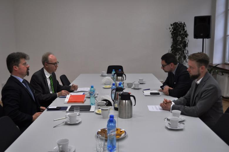 zdjęcie: czterach mężczyn siedzi przy białym stole