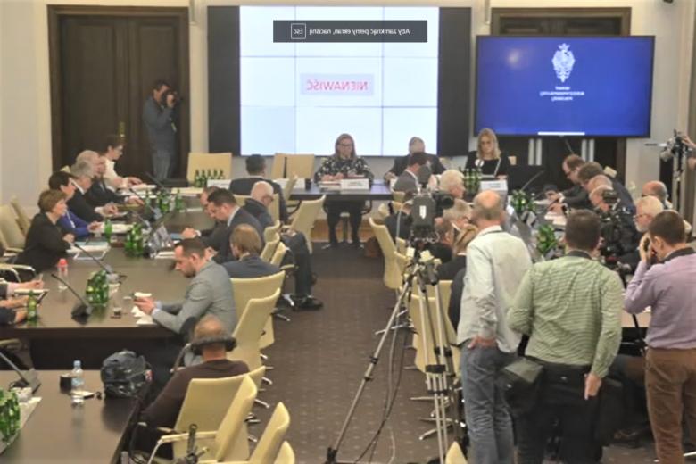 osoby siedzą za stołami w otoczeniu kamer