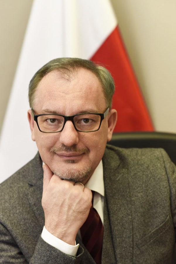 Mężczyzna w garniturze, w tle biało-czerwona flaga