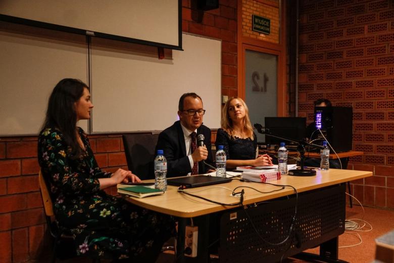 Dwie kobiety i mężczyzna przy stole panelowym