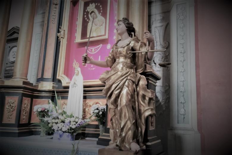 Złocista postać z wagą i mieczem na ołtarzu w kościele