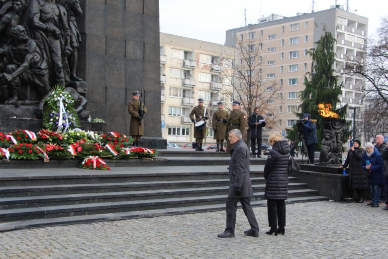 Osoby składają wieńce pod pomnikiem