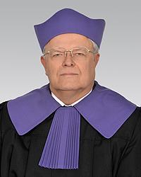 Mężczyzna w stroju sędziego - fioletowym birecie i todze z fioletowym kołnierzem
