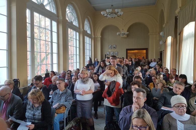Ludzie zgromadzeni na sali z wysokimi oknami