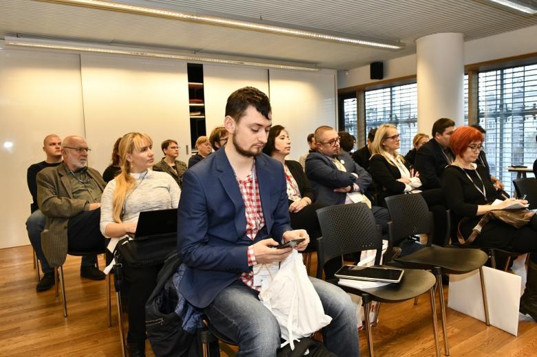 Uczestnicy warsztatu, na pierwszym planie mężczyzna sprawdza informacje w telefonie