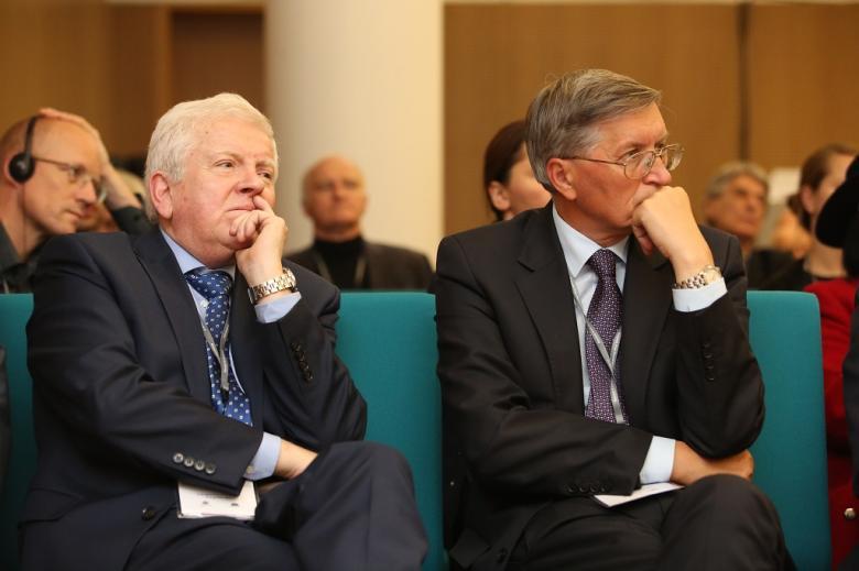 Dwaj mężczyźni w pierwszym rzędzie publiczności słuchają w skupieniu, zielone krzesła