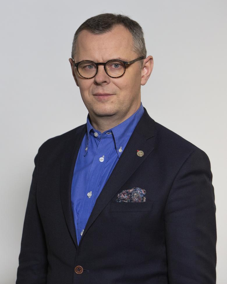 mężczyzna w marynarce z niebieską koszulą i okularami