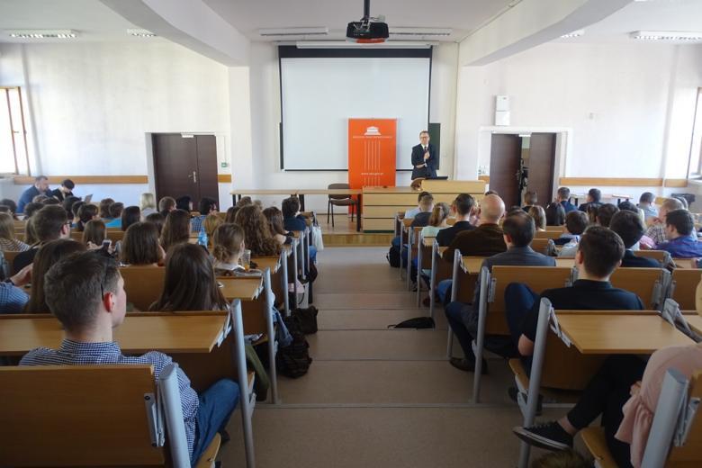 Aula uniwersytecka pełna ludzi, wykład, ujęcie na wprost wykładowcy