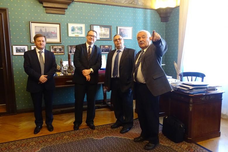 Czterej męzczyźni w zabytkowym gabinecie, siwowłosy mężczyzna wskazuje ręką przed siebie