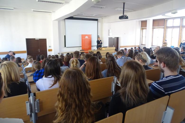 Aula uniwersytecka pełna ludzi, wykład, ujęcie ze skosu