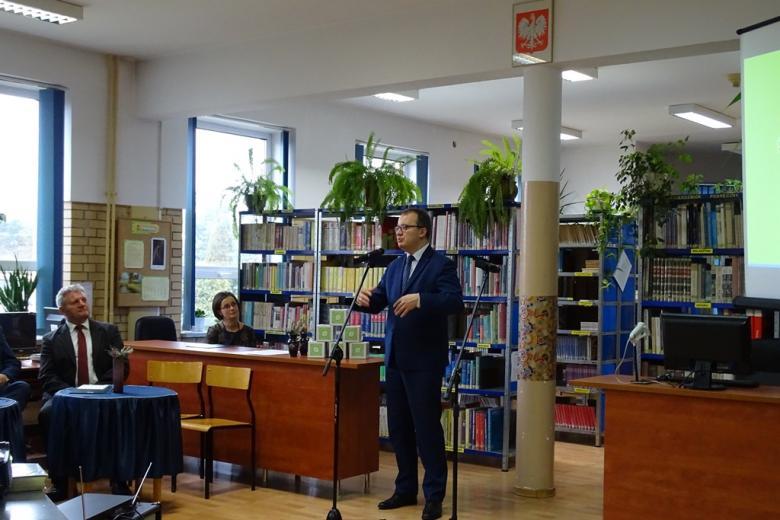Zdjęcie: mężczyzna stoi w sali bibliotecznej i mówi gestykulując