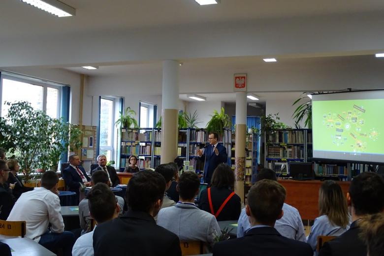 zDJĘCIE: spotkanie w bibliotece szkolnej. Ludzie słuchają, mężczyzna opowiada gestykulując