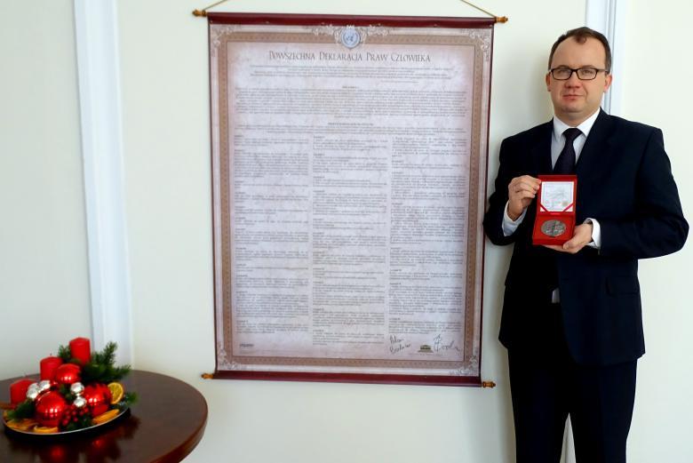 zdjęcie: mężczyzna w garniturze stoi po prawej stronie i trzyma w dłoniach pudełko ze srebrnym medalem, za nim wisi tekst Powszechnej Deklaracji Praw Człowieka, a po lewej stronie widać stolik ze świątecznym stroikiem