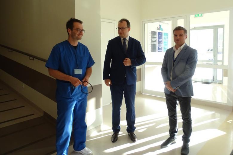 Zdjęcie: trzej mężczyźni w jasnym wnętrzu, jeden w granatowym stroju lekarza