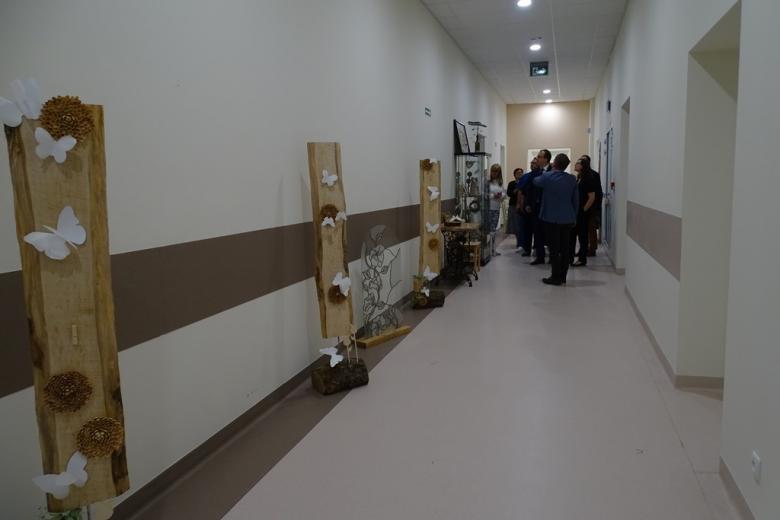 Zdjęcie: jasny korytarz z pracami artystycznymi, w głębi - ludzie