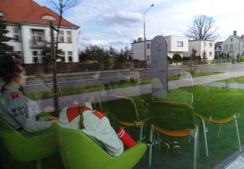Widok na salę biblioteczną z ulicy. Widać ludzi, a w szybie odbija się ulica