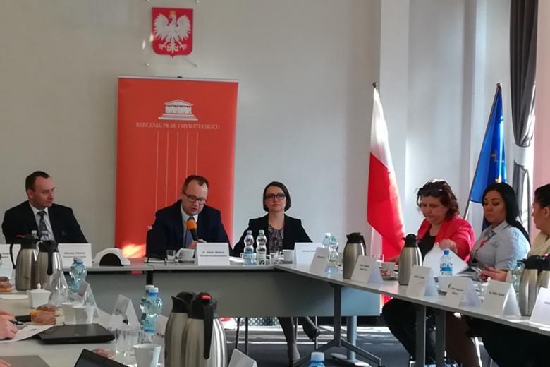 Kobiety i mężczyźnie przy czworokątnym stole, z tyłu banner RPO oraz flagi Polski I UE