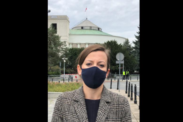 kobieta w maseczce ochronnej przed Sejmem