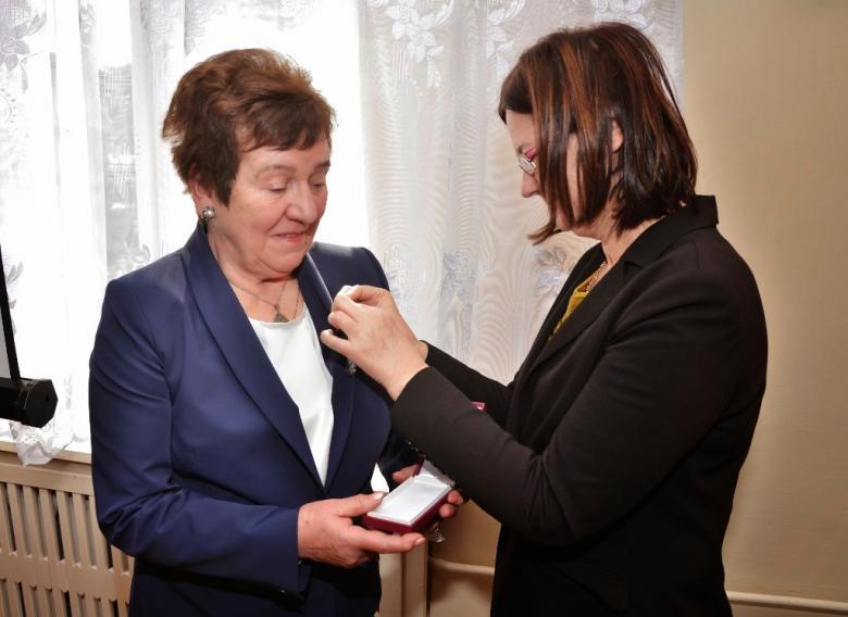 Kobieta przypina odznakę drugiej kobiecie