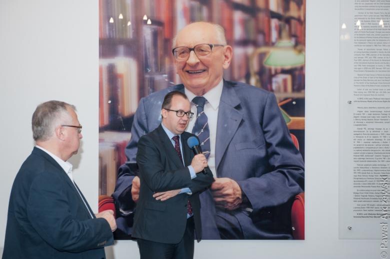 zdjęcie: dwóch mężczyzn w garniturach stoi, jeden z nich mówi do mikrofonu
