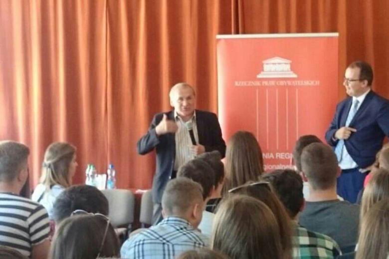 Zdjęcie: mężczyzna mówi do młodych ludzi siedzących na sali