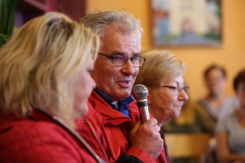 Mężczyzna ubrany na czerwono mówi