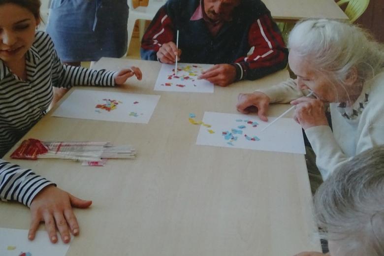 Ludzie przy stole układają kolorowe wzory na papierze