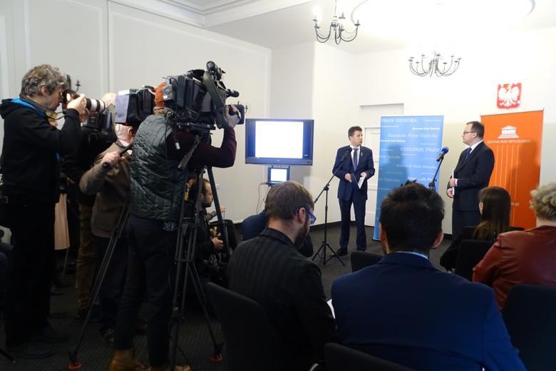 Konferencja prasowa - dziennikarze, kamery i dwaj męzczyźni na tle bannerów RPD (niebieskiego) i RPO (pomarańczowego)