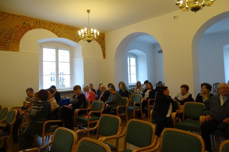 Ludzie w zabytkowej sali czekają na rozpoczęcie spotkania