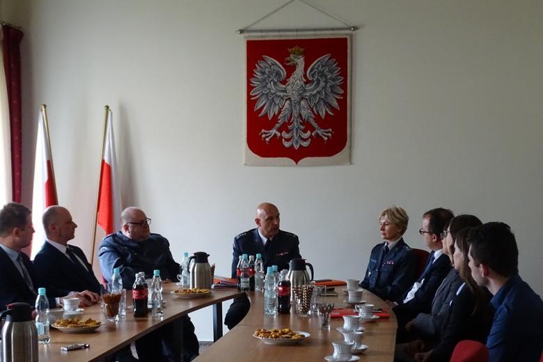Zdjęcie: ludzie przy stole, trójka w mundurach, z tyłu dwie biało-czerwone flagi i duże godło
