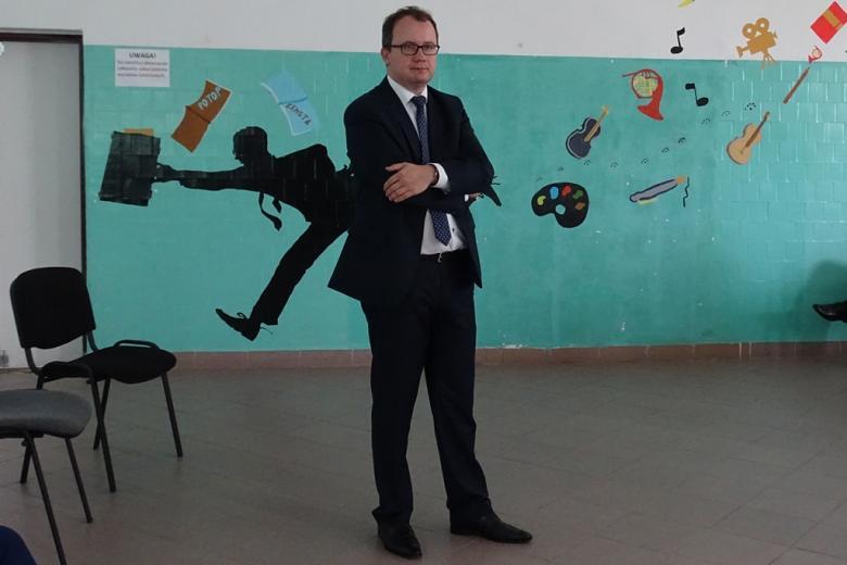 Zdjęcie: mężczyzna stoi na tle ściany, na której są rysunki i napisy