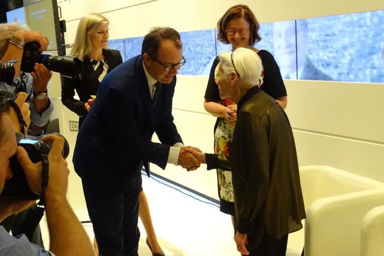 Zdjęcie: męzczyzna gratuluje odznaczonej kobiecie