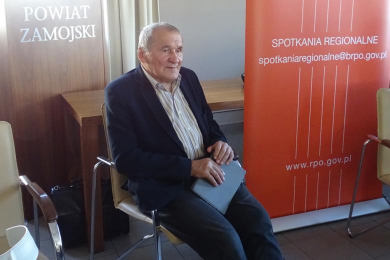 Zdjęcie: mężczyzna siedzi i uważnie słucha