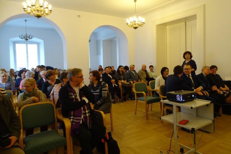 Ludzie siedzą w dużej zabytkowej sali