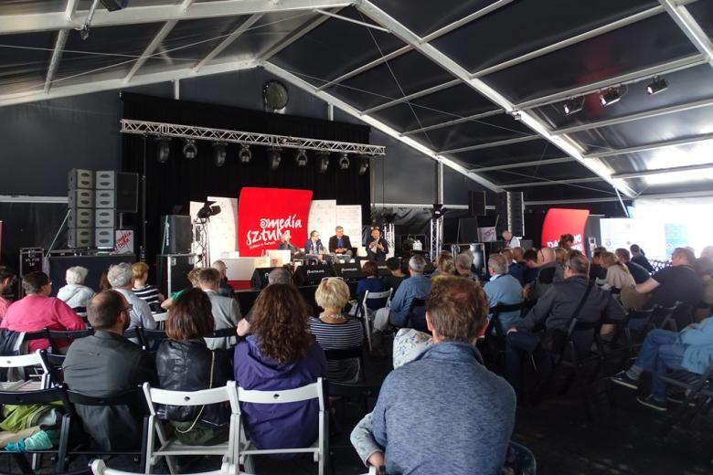 Zdjęcie: dużo ludzi słucha czterech panelistów w dużym namiocie