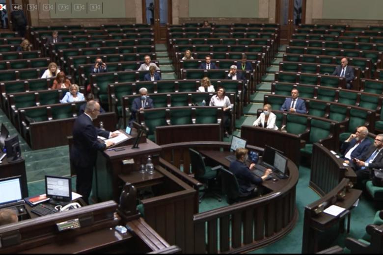 Mężczyzna na mównicy, kilkoro posłów w ławach po lewej stronie