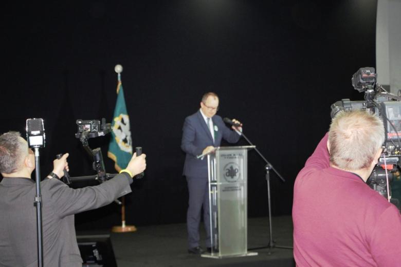 Mężczyzna na mównicy na tle ciemnej ściany i kamerzyści