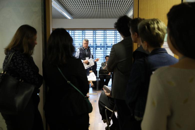 Ludzie zaglądają do wypełnionej sali przez otwarte drzwi