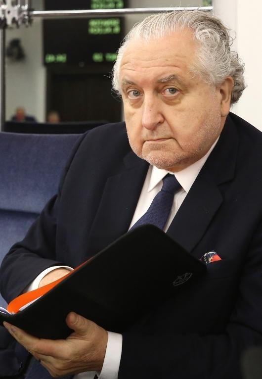 Mężczyzna w garniturze, białej koszuli i krawacie