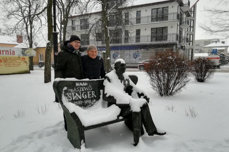 Dwaj mężczyźni przy ławeczce z figurą