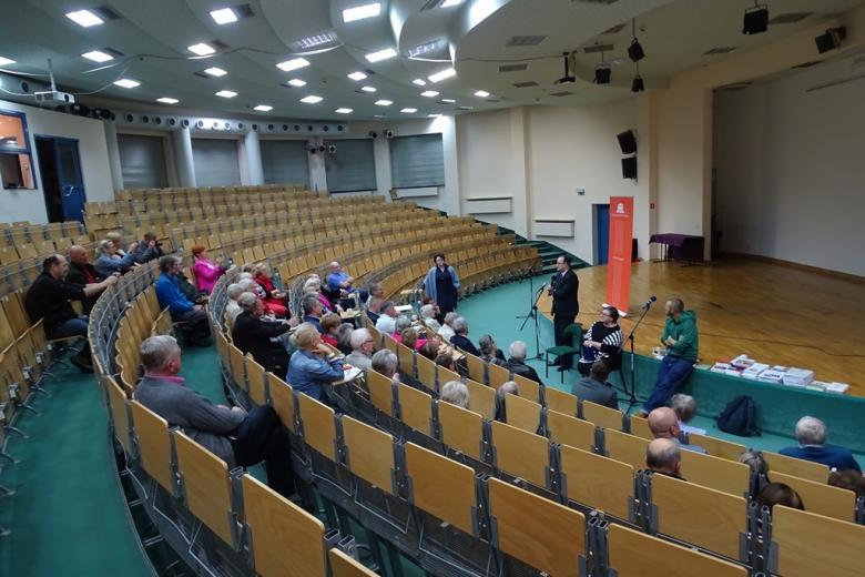 Ludzie w auli uniwersyteckiej, ujęcie z tyłu