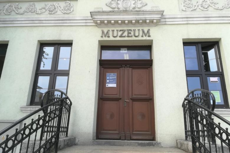 Plakat na drzwiach z napisem MUZEUM. Plakat ma symbol połaczenia