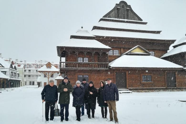 Grupa ludzi w zaśnieżonym drewnianym miasteczku, zdjęcie grupowe