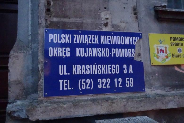 Zdjecie: niebieska tablica informacyjna na odrapanej ścianie