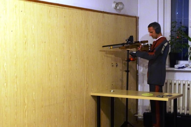 Zdjęcie: mężczyzna mierzy z broni strzeleckiej. Ma słuchawki