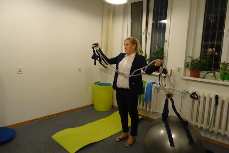 Zdjęcie: kobieta w sali gimnastycznej prezentuje uprząż