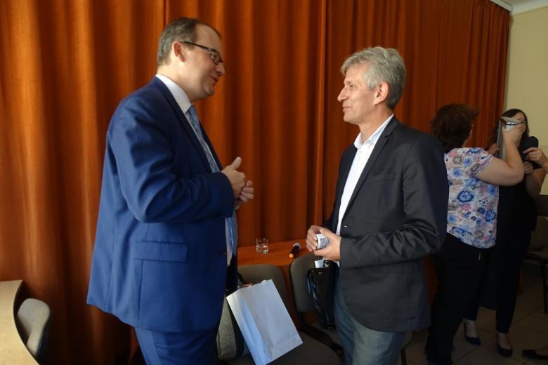 Zdjęcie: dwaj mężczyźni rozmawiają stojąc