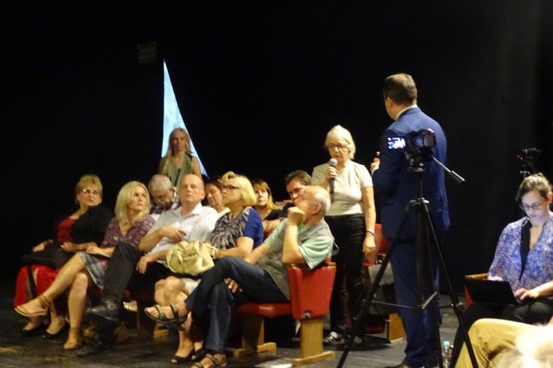 Zdjęcie: kobieta mówi do mikrofonu mężczyzna słucha na stojąco